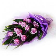 Mano Ramo de rosas púrpuras con los llenadores y follaje