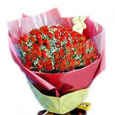 Ramo de rosas rojas de 100 con zonas verdes y un pequeño oso de peluche