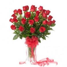 Tres docenas de rosas en un florero de vidrio