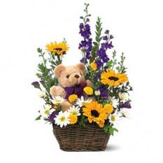 Cesta de flores de primavera y un oso de peluche