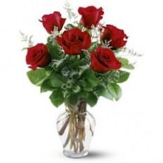 Seis rosas en un florero de vidrio