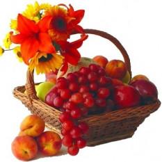 Canasta de frutas con lirios y girasoles o gerberas