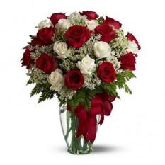 Dos docenas de rosas rojas y blancas en un jarrón de vidrio